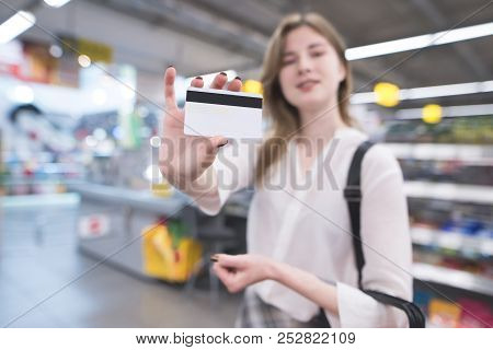 Happy Woman Is In The Supermarket And Shows A Credit Card. Credit Card Is In The Hands Of The Buyer