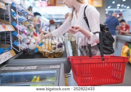 Girl With Red Basket Standing At The Checkout In The Supermarket. Focus On Shopping Cart. Payment Pr