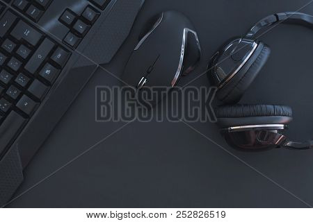 Black Mouse, The Keyboard, The Headphones Are Isolated On A Dark Background, The Top View. Flat Lay