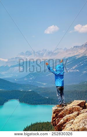 A Hiker Standing On The Edge Of Bow Summit Overlooking Peyto Lake In Banff National Park On The Icef