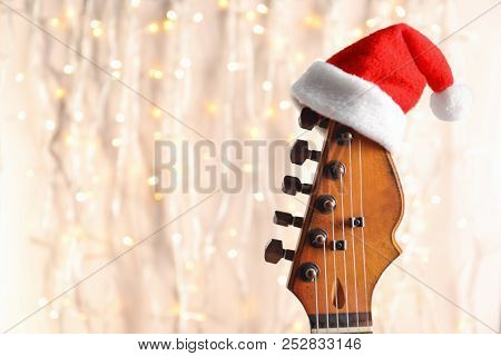 Guitar With Santa Hat On Blurred Background. Christmas Music Concept