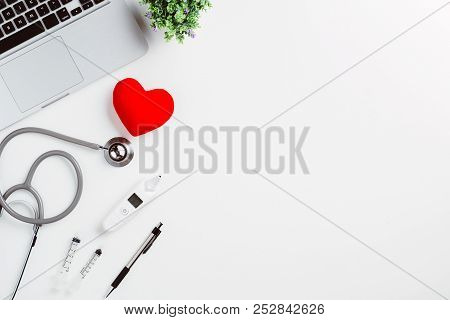 Medical Desk With Stethoscope,heart,pen,laptop,mouse And X-ray Film On White Desk.top View With Copy