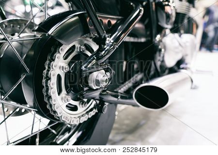Detail Of A Motorcycle Rear Chain With Exhaust Pipes. Rear View Of A Motorcycle With The Focus On Ch