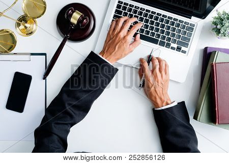 Male Judge Working With Laptop Computer On White Wooden Table In Courtroom.justice And Law Concept.t