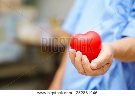 Asian Senior Or Elderly Old Lady Woman Patient Holding Red Heart In Her Hand On Bed In Nursing Hospi