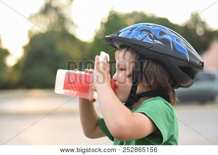 Little Cyclist With A Helmet Drinks Water. Boy On Bicycle Drink Water