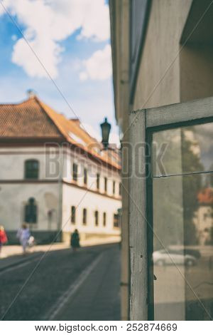 City Life Is Reflected In An Open Window With A Crack In The Street Of The Old City Of Vilnius