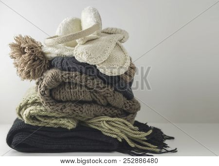 Warm Woolen Knitted Winter And Autumn Clothes, Folded In A Pile On A White Table. Sweaters, Scarves,