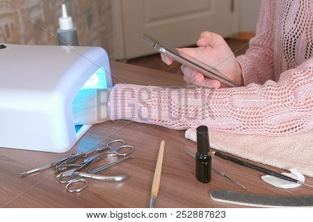 Woman Dries Her Nails With Shellac In Uv Lamp And Browsing Internet In Mobile Phone. Close-up Hand.