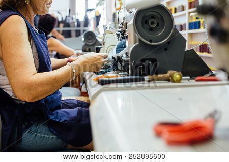 Side View Of A Woman Sewing A Piece Of Leather With The Sewing Machine To Upholster A Car Seat In A