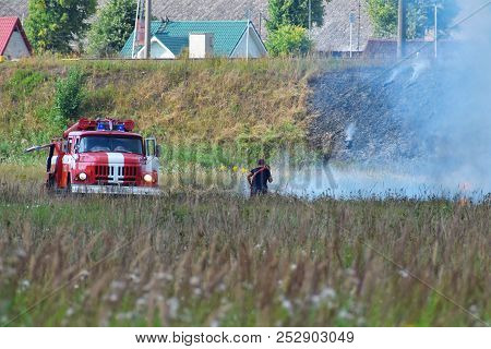 Fire Truck And Firefighter On Firefighting Rescue Operation Fighting With Flames In Burning Meadow N