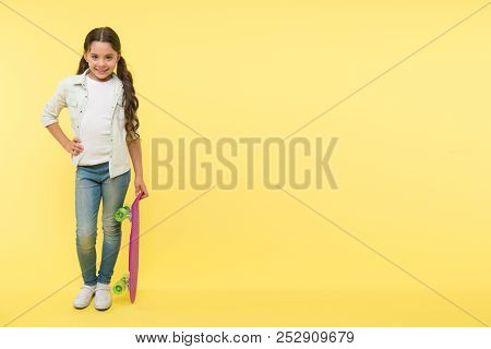 Her Favorite Activity. Kid Girl Happy Holds Penny Board. Child Likes Skateboarding With Penny Board.