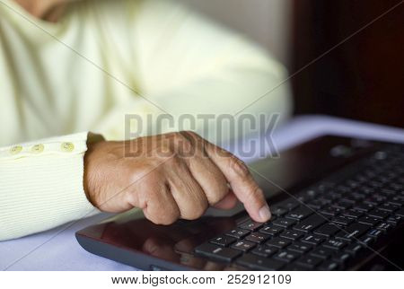 Closeup Senior Old Woman Hand On Laptop Keyboard Surfing And Browsing Internet At Home With Free And