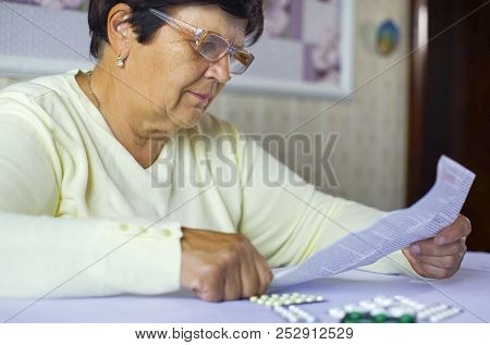 Senior Woman Reading Information Sheet Of Prescribed Medicine Sitting At Table At Home. Pharmacy, Ag