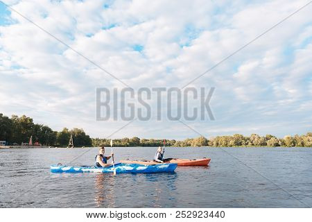 Husband Sitting In Blue Canoe Rowing Near His Woman In Red Canoe