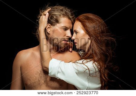 Real Passion. Beautiful Young Loving Couple Bonding To Each Other While Both Standing Against Black