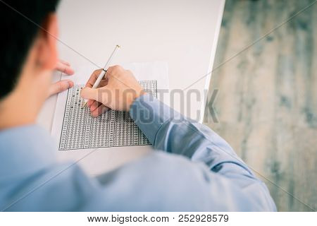 Back View Of Man Filling Out An Answer On Answer Sheet During Exam