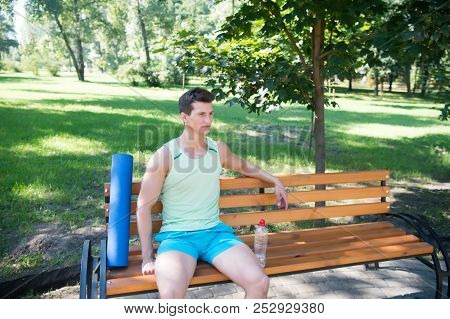 Workout Is Over. Man With Yoga Mat And Water Bottle Sit On Bench In Park. Join Outdoors Yoga Practic