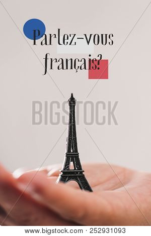 a miniature of the Eiffel Tower on the hand of a young man and the question parlez-vous francaise, do you speak French? written in French, against an off-white background