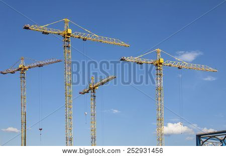 Tower Crane At The Construction Site Against The Blue Sky
