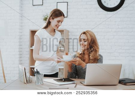 Smiling Young Daughter Giving Working At Home Mother Cup Of Coffee. Daughter Helping Mother. Mother