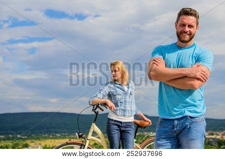 Man Bearded Macho Posing Confidently In Front Of Shy Girl With Bike. Cycling Instructor Concept. Nev