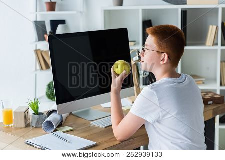 Preteen Ginger Hair Boy Holding Apple Near Computer At Home