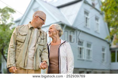 old age, accommodation and real estate concept - happy senior couple holding hands over living house background