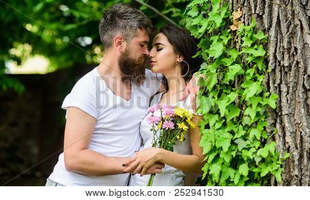 Gentle kiss. Man bearded hipster hugs gorgeous girlfriend. Couple in love going to kiss. Pleasant romantic kiss. Couple love romantic date nature park background. Love relations romantic feelings poster