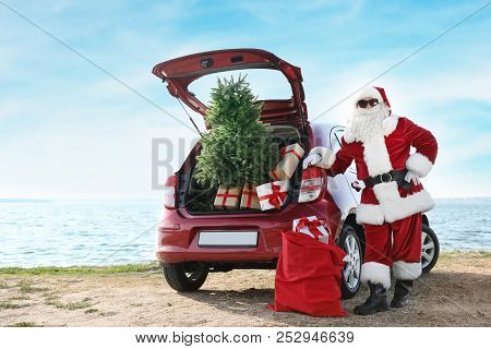 Authentic Santa Claus Near Red Car With Gift Boxes And Christmas Tree On Beach