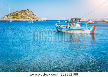 Colorful Greek Fishing Boat At The Calm Clear Water On Early Summer Morning. White Rock At The Backg