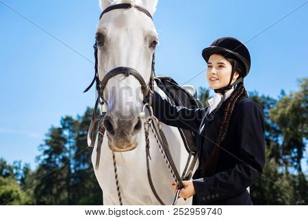 Beautiful dark-eyed female rider with fishtail Professional racehorse. poster