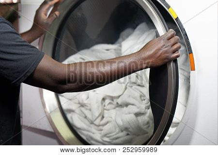 The Hands Of An African Male Laundry Worker In The Inn Give A Clean Towel From The Washing Machine.