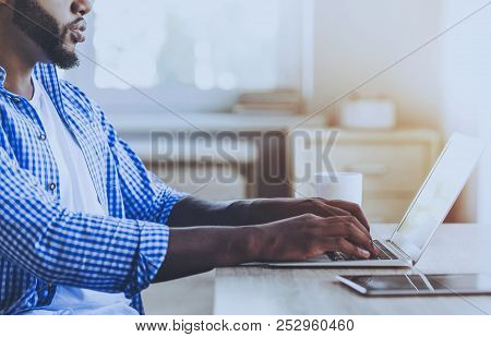 Young Beard Afro-american Man Working With Laptop Sitting At Table. Freelancer At Home. Work Concept
