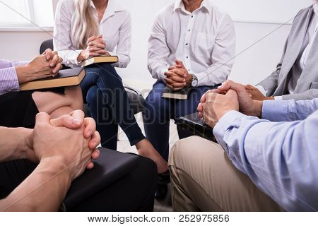 Group Of People Sitting Together Praying With Holy Bible
