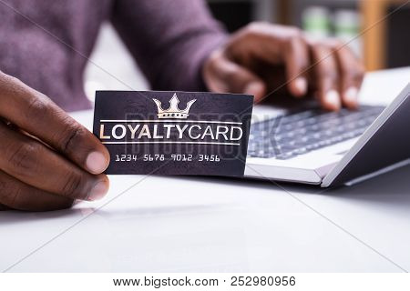 Close-up Of A Person Holding Loyalty Card Using Laptop