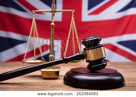 Close-up Of Judge Wooden Gavel And Justice Scale In Front Of Uk Flag