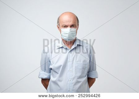 Portrait Of Serious Man In Special Medic Mask. He Is Looking Serious. Mature Experienced Doctor.