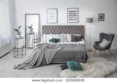 Elegant Room Interior With Large Comfortable Bed And Armchair