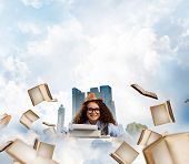 Young and beautiful woman writer in hat and eyeglasses using typing machine while sitting at the table among flying books with floating city island and cloudy skyscape on background. poster
