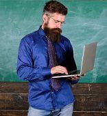 Online education. Modern technology education. Hipster teacher wear eyeglasses and necktie holds laptop. Digital technology education. Teacher bearded man with modern laptop chalkboard background poster