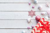christmas festive background. glittery adornments and embellishments. gift box with red chevron pattern and assortment of balls and toys scattered on the white backdrop. poster