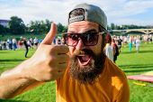 Top list summer festival must visit. Highly recommend top list. Hipster visiting event picnic fest or festival. Man cheerful face shows thumb up. Man bearded in front of crowd riverside background poster
