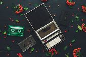 Flat lay music audio cassette and player, nostalgic image top view of retro technology from 80s and 90s with wild berry fruit decoration arrangement poster
