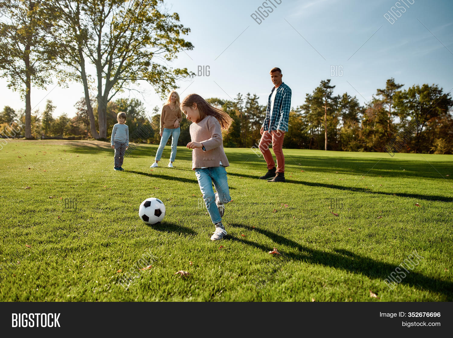 Portrait Of Cheerful Little Girl Playing Football With Her Family In The Park On A Sunny Day. They A