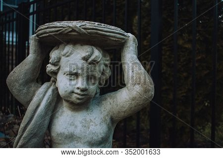 A Close Up Shot Of A Gray Statue Of A Cherub Holding An Empty Plate With Trees In The Background