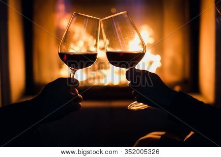 Young Couple Have Romantic Dinner With Wine Over Fireplace Background