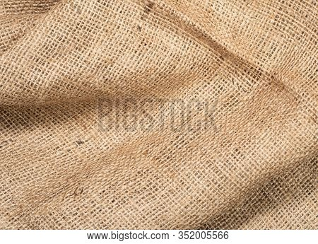 Texture Of Brown Burlap Fabric, Close Up View. Crumpled Burlap Linen, Abstract Background. Brown Hop