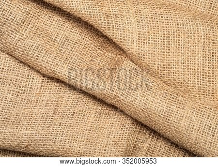 Close Up View On Brown Burlap Textile. Texture Of Brown Baline. Crumpled Burlap Fabric, An Abstract