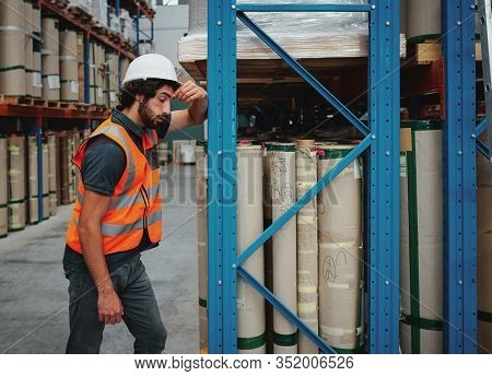 Stressed Factory Worker Suffering Head Pain Migraine Or Headache Rubbing His Temples